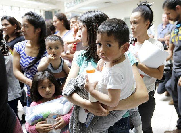 women-and-children-wait-inside-a-bus-station-friday-after-they-were-processed-and-released-by-us-customs-and-border-protection-in-mcallen-texas