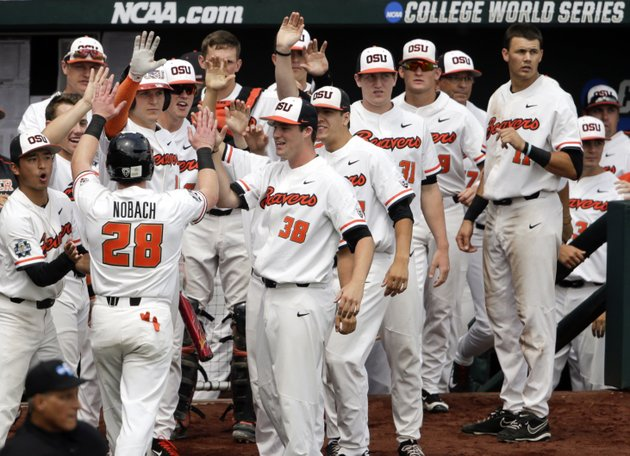 oregon-states-kyle-nobach-28-is-greeted-at-the-dugout-after-he-scored-against-mississippi-state-on-a-one-run-single-by-michael-gretler-in-the-second-inning-of-an-ncaa-college-world-series-baseball-game-in-omaha-neb-friday-june-22-2018-ap-photonati-harnik