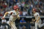 Arkansas third baseman Casey Martin (foreground) runs to first base, while first baseman Jared Gates (background) runs toward home plate during the sixth inning of a College World Series game against Florida on Friday, June 22, 2018, in Omaha, Neb.