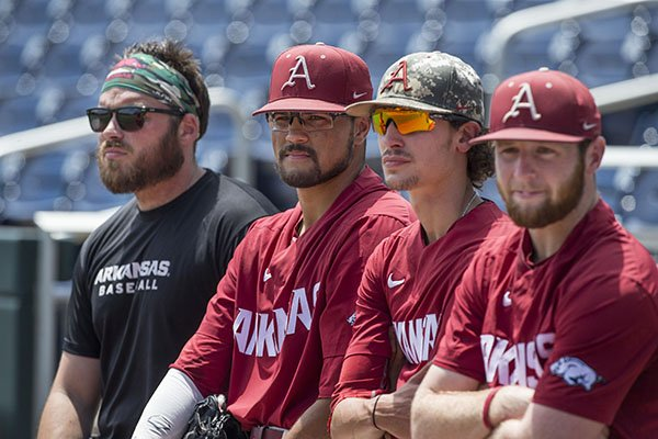 From left: Arkansas strength coach Blaine Kinsley and pitchers Isaiah Campbell, Blaine Knight and Matt Cronin watch during practice Sunday, June 24, 2018, in Omaha, Neb.