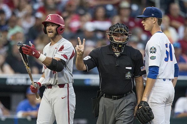 Arkansas designated hitter Luke Bonfield, left, contends he was interfered with while home plate umpire Travis Katzenmeier, center, and Florida pitcher Brady Singer look on during a College World Series game Friday, June 22, 2018, in Omaha, Neb.
