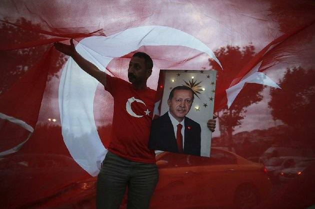 a-man-holds-a-picture-of-recep-tayyip-erdogan-turkeys-president-and-ruling-justice-and-development-party-leader-while-celebrating-outside-the-party-headquarters-sunday-in-istanbul