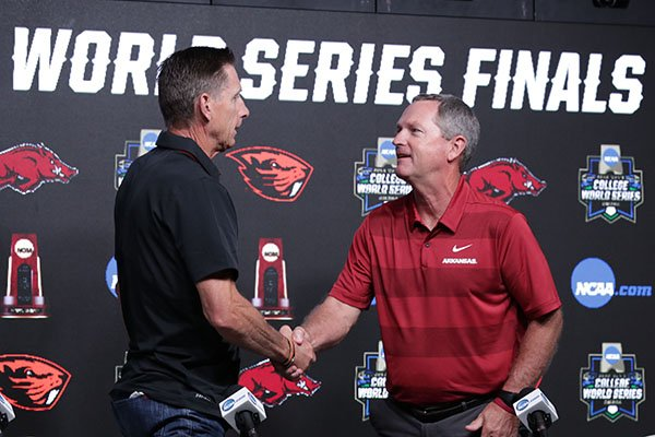 Arkansas coach Dave Van Horn, right, shakes hands with Oregon State coach Pat Casey following a news conference Sunday, June 24, 2018, at the College World Series in Omaha, Neb.