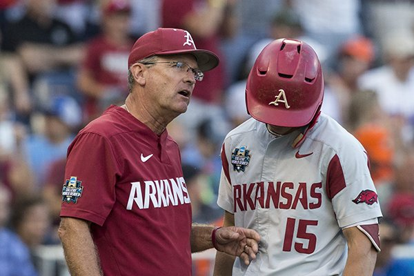 Arkansas coach Dave Van Horn, left, talks with third baseman Casey Martin during a College World Series finals game Tuesday, June 26, 2018, in Omaha, Neb.