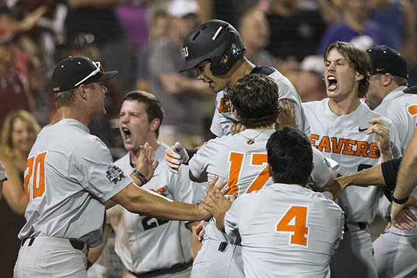 Oregon State players celebrate after Trevor Larnach hit a home run during the ninth inning of a College World Series final game against Arkansas on Wednesday, June 27, 2018, in Omaha, Neb.