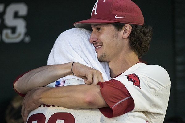 Arkansas pitcher Blaine Knight, facing, hugs catcher Grant Koch after the Razorbacks lost to Oregon State in the College World Series championship game on Thursday, June, 28, 2018, in Omaha, Neb.