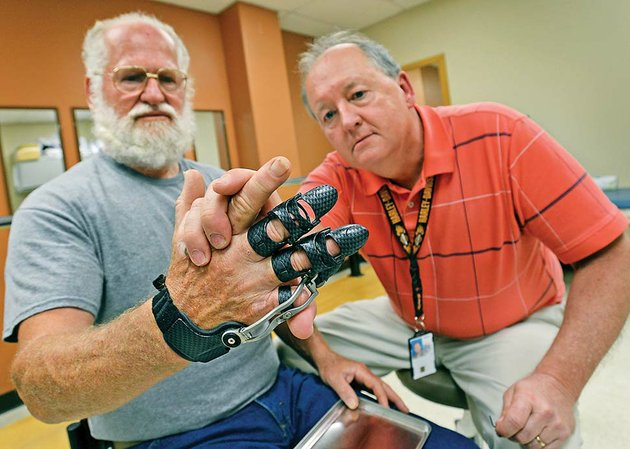 navy-veteran-fred-fuquay-left-and-steve-street-a-prosthetist-with-the-central-arkansas-veterans-health-system-observe-the-dexterity-of-fuquays-new-articulating-hand-prosthetic-during-a-fit-check-may-22-at-the-cavhs-prosthetics-service-clinic-after-fuquay-lost-his-middle-and-pinkie-fingers-in-a-workplace-accident-health-system-specialists-provided-him-a-custom-fit-titanium-and-carbon-fiber-device-that-gives-him-greater-mobility-dexterity-and-hand-function