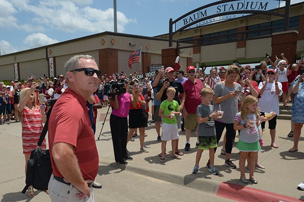 Arkansas coach Dave Van Horn smiles Friday, June 29, 2018, while watching his players and staff exit a bus as fans line the sidewalk at Baum Stadium in Fayetteville to welcome back the Razorback baseball team from its trip to the College World Series.