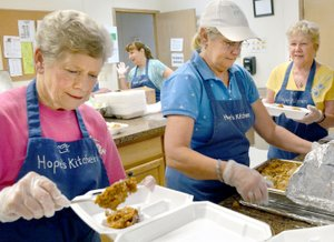 Janelle Jessen/Siloam Sunday Volunteers, from left, Judy Blank, Georgia Loyd and Maryette Womack made plates of food at Hope's Kitchen.