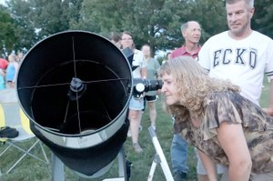 LYNN KUTTER ENTERPRISE-LEADER Melissa Hoffman of Prairie Grove looks through one of the telescopes set up for a Star Party at Prairie Grove Battlefield State Park.