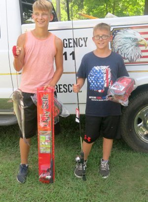 Westside Eagle Observer/SUSAN HOLLAND Brothers Hunter and Evan Carter, sons of Joe and Sheri Carter, display their fish and the prizes they won in the Sulphur Day fishing derby. Both were first-place winners in their age groups. Hunter, 13, took the 12-16 age division with a 16 1/4-inch fish; and Evan, 11, won the 6-11 age division with a 16 3/4-inch fish. Their prize tackle boxes and Ugly Stik rods were furnished by the Arkansas Game and Fish Commission.
