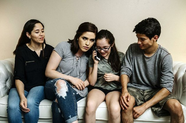 yadira-lopez-looks-on-as-her-children-juana-barrios-andrea-barrios-and-oscar-barrios-speak-by-phone-with-their-father-who-was-detained-in-iowa-by-immigration-authorities-in-may