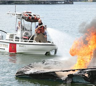 Members of the Lake Hamilton Fire department extigush a boat fire on Friday July 6. One man and woman reportedly were able to swim safely to shore. No injuries were reported. The cause of the fire is still unknown. (The Sentinel-Record/Rebekah Hedges)