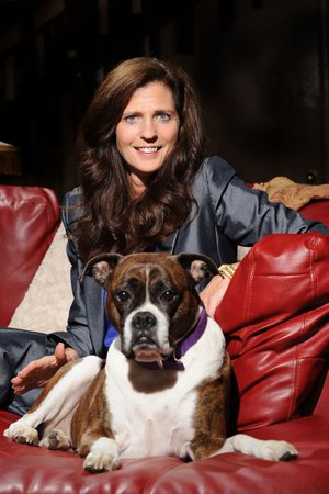 NWA Media/ANDY SHUPE - Betsy Broyles Arnold, seen here with her dog, Emma, is the daughter of longtime University of Arkansas football coach and athletics director Frank Broyles and is the founder of the Broyles Foundation/Caregivers United. Thursday, July 3, 2014.