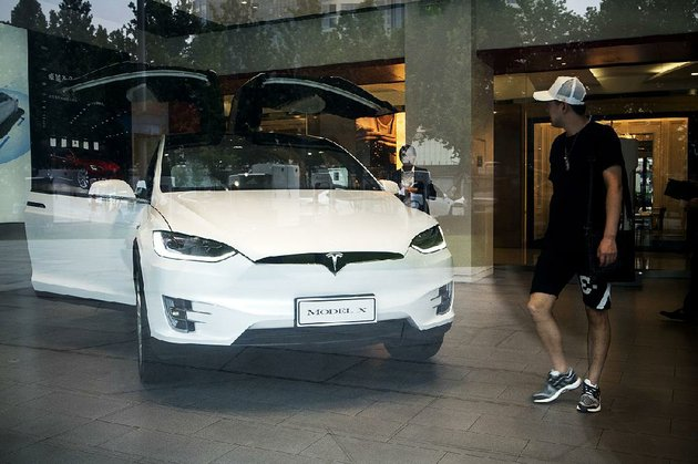 a-customer-looks-at-a-tesla-model-x-electric-vehicle-on-display-saturday-at-the-companys-showroom-in-beijing-tesla-has-sold-cars-in-china-since-2014-but-the-company-ships-them-from-its-factory-in-california