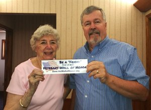 """Courtesy photo Julie Storm (left) is an associate member of the Veterans' Wall of Honor, and Douglas Grant is president of the Veterans' Council of Northwest Arkansas. Both are shown holding the """"Friends of the Wall of Honor"""" bumper sticker."""