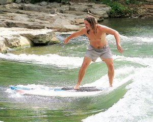 Westside Eagle Observer/RANDY MOLL Jonnie Brown, of Gentry, tests his skill at surfing in the whitewater of Siloam Springs Kayak Park on July 3. He and Dalton Morris, also of Gentry, used paddle boards in the river.