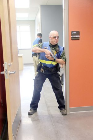 """LYNN KUTTER ENTERPRISE-LEADER Hunter Carnahan, school resource officer with Greenland School District and a volunteer firefighter with Farmington Fire Department, stands guard following an active shooter training scenario at Farmington High earlier this summer. The """"shooter"""" is dead in the classroom behind him and several people are """"injured."""" Participants were learning about an integrated response that uses law enforcement, firefighters and other first responders."""