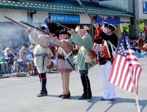 Lynn Atkins/The Weekly Vista Members of a group of Revolutionary War re-enactors fired muskets at the start of the 12th annual Fourth of July Patriots Parade in Sugar Creek Center on July Fourth.
