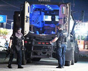 The Sentinel-Record/Grace Brown SWAT TEAM: Members of the Hot Springs Police Department's SWAT team exit the department's Mine Resistant Ambush Protected vehicle following the conclusion of a two-hour standoff with a suspect at Timbercrest RV & Mobile Home Park, 3921 Central Ave., Monday night.