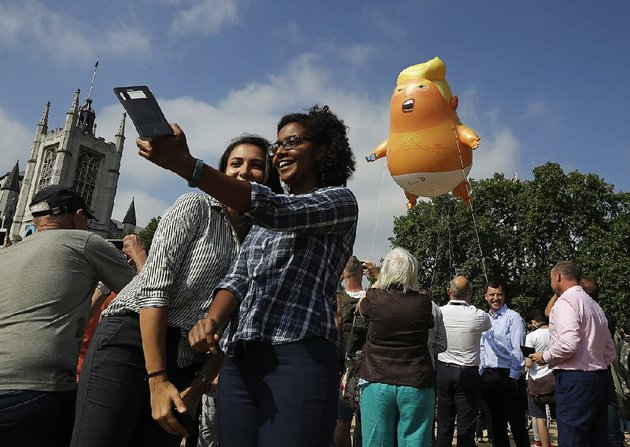 people-in-londons-parliament-square-take-photos-of-a-balloon-depicting-president-donald-trump-as-an-angry-baby-that-was-flown-as-a-protest-against-his-trip-to-england