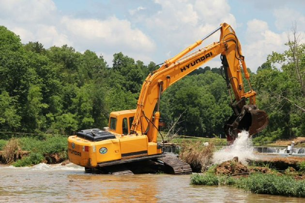 a-track-hoe-works-thursday-to-fill-in-a-sinkhole-in-the-spring-river-that-opened-last-month-and-claimed-the-life-of-a-kayaker-the-work-collapsed-the-sinkhole-roof-and-filled-in-the-opening-resolving-the-hazard