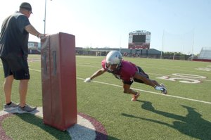 Graham Thomas/Siloam Sunday Siloam Springs head coach Brandon Craig holds a tackling dummy as senior cornerback Primo Agbehi dives in for a tackling drill at football practice Thursday at Panther Stadium.