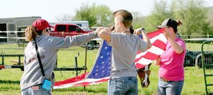 Submitted photo Members of Lincoln Riding Club's precision drill team known as 'The Regulators' and participants in an April 29 clinic conducted by the team fold an American flag. 'The Regulators' proudly carry the U.S. and other flags on horseback during rodeo performances.
