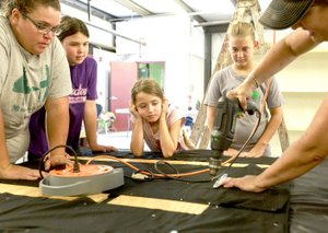 NWA Democrat-Gazette/CHARLIE KAIJO Shannon Brown of Maysville (right) drills as Tonya Farrister, Kelli McGarrah, 10, Kinzie McGarrah, 7 and Laney Brown, 13, from the Maysville 4-H Club (from left) watch, Saturday, August 4, 2018 at the Benton County Fairgrounds in Bentonville. Vendors prepared their booths ahead of the Benton County Fair which is set to begin August 7.