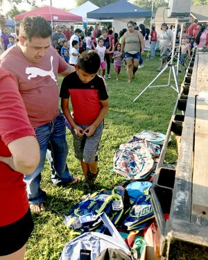 Sally Carroll/McDonald County Press Jose Hernandez-Lopez (left) guides his son, Josque, while he tries to find the perfect backpack. Several lucky winners were able to pick out a backpack at the Noel First Friday/Back-To-School Bash. The Noel Betterment Association teamed up with the Noel Elementary and Primary schools to host the event, which drew a huge crowd to enjoy games, music, a free waterslide, treats and more.