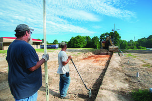 County employees Tuesday begin dirt work on a new parking lot set to be laid at the entry of the former West Side Elementary school at 101 Boundary Street in Magnolia. The site was purchased from the local public school district in 2017 by the county as new home for its offices currently occupying in the downtown Annex Building. The project is scheduled to be completed by year's end.