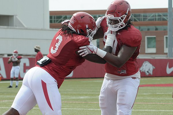 Arkansas defensive linemen Armon Watts (right) and McTelvin Agim go through a drill during practice Wednesday, Aug. 8, 2018, in Fayetteville.