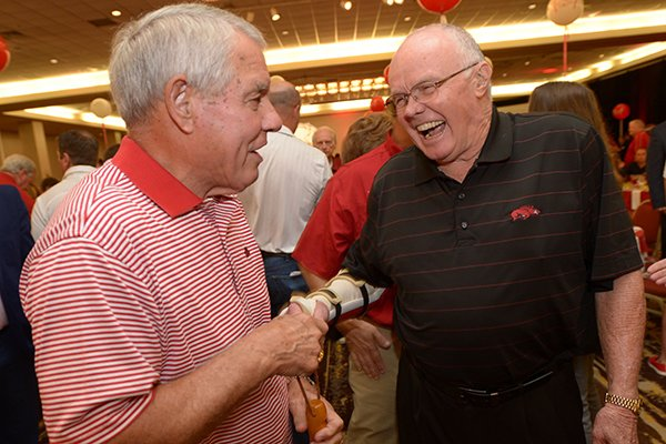 Ken Hatfield (left) shares a laugh Friday, Aug. 17, 2018, with Jesse Branch during the annual Kickoff Luncheon at the Northwest Arkansas Convention Center in Springdale.