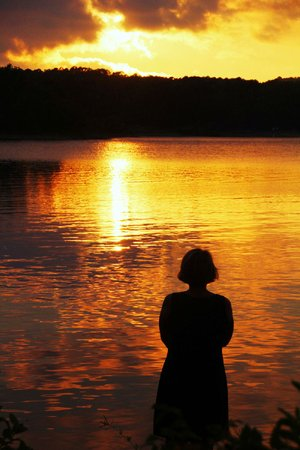 At the edge of an island in Lake Ouachita, camper Jill Skaggs enjoys a moment of Zen as the sun sets July 28.