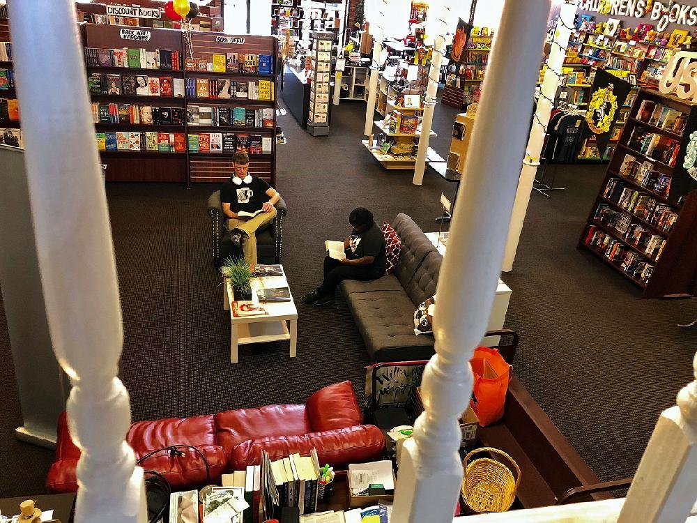 Seen from a balcony study area Aug. 28, David Peterson (left) and Denise Head enjoy the lounge area at Dog Ear Books.