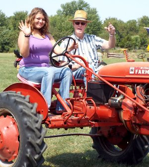 Westside Eagle Observer/RANDY MOLL Makayla Henson, a student at Rogers Heritage High School, takes a tractor-driving lesson from Glenn Smith, member of the Tired Iron of the Ozarks, and drove with him in the noon Parade of Power on one of his dual-seat and dual-control Farmall tractors during the opening day of the fall show of the Tired Iron club on Sept. 8, 2017. This year's fall show begins on Friday.