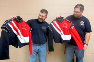 Westside Eagle Observer/SUSAN HOLLAND Aaron Ray, band director at Gravette High School, and Mark Hendrick, middle school band director, examine jackets from the high school marching band uniforms. Uniforms that needed cleaning were picked up Friday, Aug. 31, for cleaning by John Guffey of Snappy Dry Cleaning in Siloam Springs. Ray said it was a welcome donation since the uniforms had not been cleaned in several years.