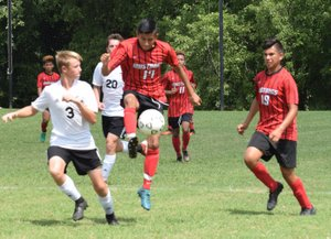 RICK PECK/SPECIAL TO MCDONALD COUNTY PRESS McDonald County's Brian Lopez goes up to settle a pass during the Mustangs' 2-1 loss to New Covenant Academy on Sept. 1 in the championship game of the Cassville High School Soccer Tournament.