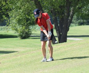 RICK PECK/SPECIAL TO MCDONALD COUNTY PRESS McDonald County's Lily Allman hits a chip shot on the first hole at Elk River Golf Course in Noel during a match with Gravette High School. The Lady Lions claimed a 147-156 win over the Lady Mustangs.
