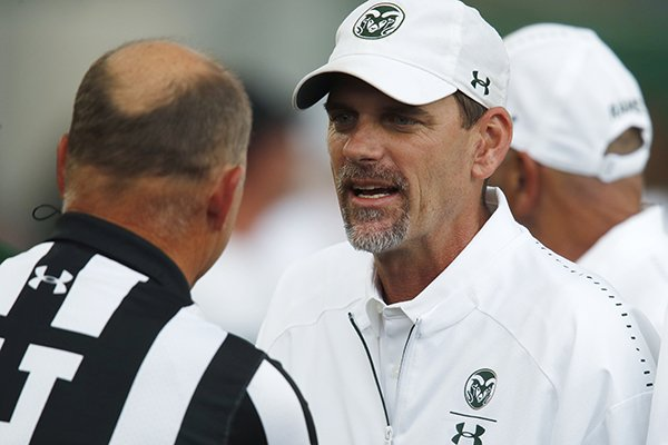 Colorado State Rams head coach Mike Bobo, right, confers with head linesman Mike Moeller before facing Hawaii in the first half of an NCAA college football game Saturday, Aug. 25, 2018, in Fort Collins, Colo. Bobo, who was just released from hospital after battling a bout of peripheral neuropathy, directed his team from the press box. (AP Photo/David Zalubowski)