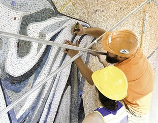 The Sentinel-Record/Grace Brown JESUS MOSAIC: Erin Holliday, left, and Vance Henson work to restore a large mosaic of Jesus Christ featured on the side of First United Methodist Church on Wednesday.