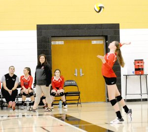 TIMES photograph by Mark Humphrey Lady Blackhawks volleyball coach Jessica Woods watches a serve during Thursday's match at Prairie Grove won by the Lady Blackhawks in three straight sets.
