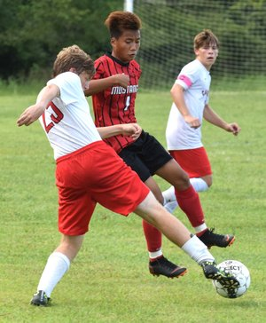 Rick Peck/Special to McDonald County Press McDonald County's Kaw Htoo and Carl Junction's Caleb Gau fight for control of a loose ball during the Bulldogs' win in penalty kicks on Sept. 6 at MCHS.
