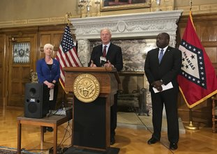 Arkansas Gov. Asa Hutchinson, center, talks at a news conference at the State Capitol in Little Rock on Wednesday about the state's work requirement for its expanded Medicaid program. Officials said more than 4,300 people on the program lost coverage for not meeting the new work requirement. (AP Photo/Andrew DeMillo)