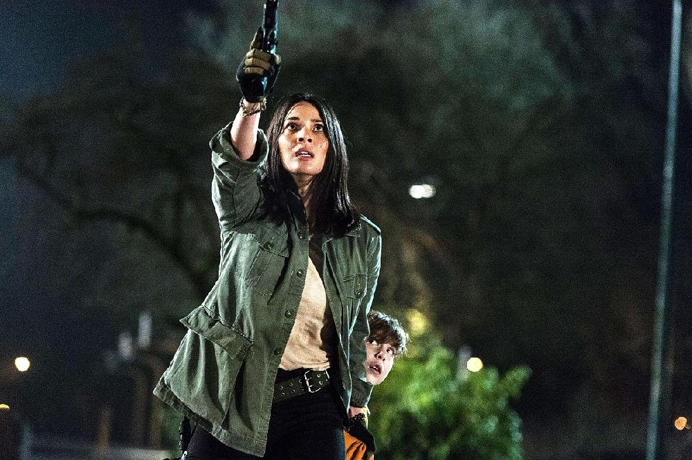 Dr. Bracket (Olivia Munn) is protective of human decoder ring Rory (Jacob Tremblay) in Shane Black's The Predator.