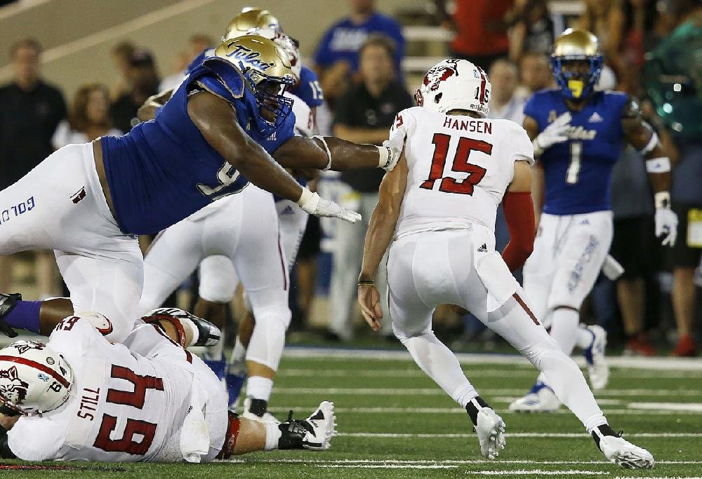 Arkansas State quarterback Justice Hansen looks to elude the  pass rush of Tulsa's Tyarise Stevenson on Saturday during the Red Wolves' 29-20 victory over the Golden Hurricane in Tulsa. Hansen led ASU with 80 rushing yards on 14 carries and went 20 of 33 passing for 191 yards.