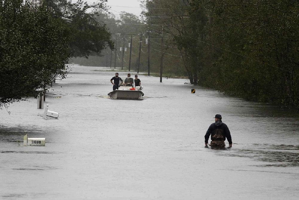 A member of the U.S. Coast Guard wades through high water Saturday in Newport, N.C., to check houses for trapped people.