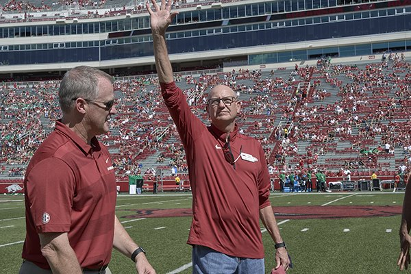 Rickey Medlock, right, waves after being introduced during halftime of Arkansas' game against North Texas on Saturday, Sept. 15, 2018, in Fayetteville. Medlock was a 2018 inductee into the UA Sports Hall of Honor.