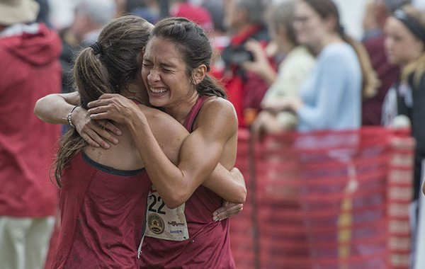 Carina Viljoen (left) and Taylor Werner embrace Saturday Sept. 22, 2018, after finishing the collegiate women's 5K race at the 30th annual Chile Pepper Cross Country Festival in Fayetteville.