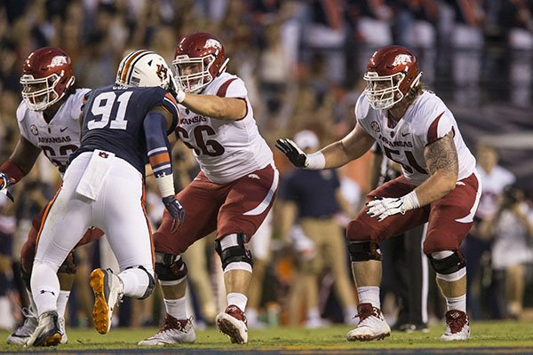Arkansas offensive linemen Johnny Gibson (62), Ty Clary (66) and Hjalte Froholdt (51) fall into pass protection while Auburn defensive lineman Nick Coe (91) applies pressure during a game Saturday, Sept. 22, 2018, in Auburn, Ala. Froholdt and Clary swapped positions for the game, a move that is expected to continue in future weeks.